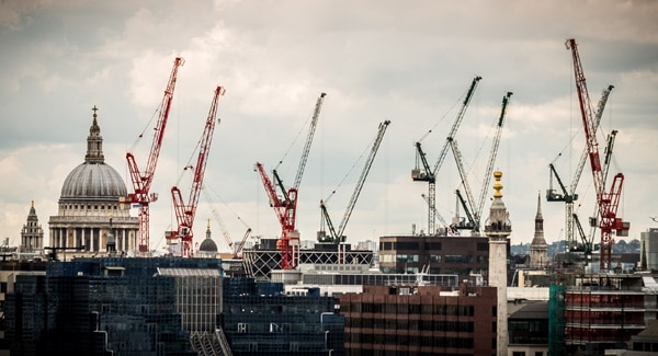 View of the iconic dome of St Pauls cathedral surrounded by cranes and construction machinery as the London skyline undergoes constant growth, development and transformation. Horizontal panoramic colour image.